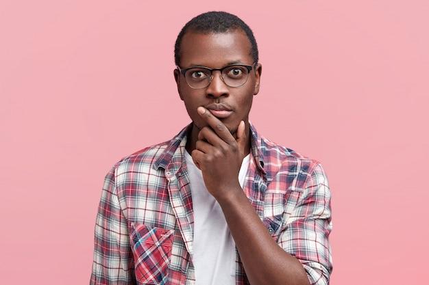 Tête d'homme sérieux à la peau sombre regarde scrupuleusement l'appareil photo, étant confiant, porte des lunettes et une chemise à carreaux, isolé sur rose
