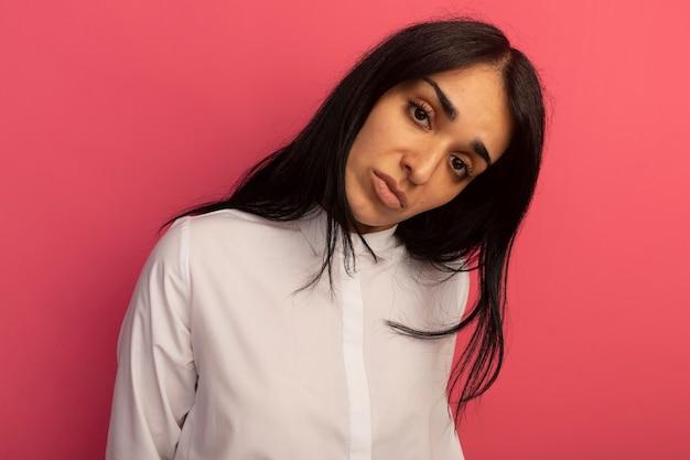 Tête inclinable jeune belle fille regardant droit devant portant un t-shirt blanc isolé sur rose