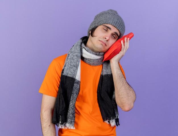 Tête inclinable jeune homme malade portant un chapeau d'hiver avec écharpe mettant le sac d'eau chaude sur la joue isolé sur violet