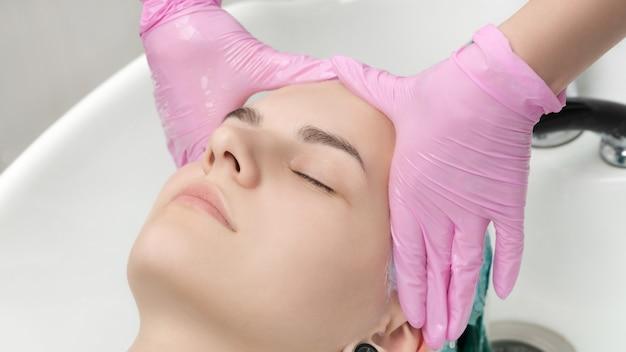 Tête de jeune femme aux yeux fermés dans l'évier dans un salon de coiffure. mains de coiffeur dans des gants lavant les cheveux dans un salon de beauté