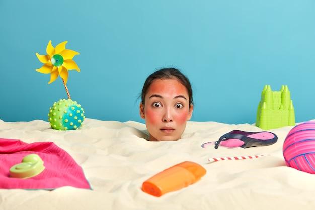 Tête de jeune femme avec crème solaire sur le visage entouré d'accessoires de plage