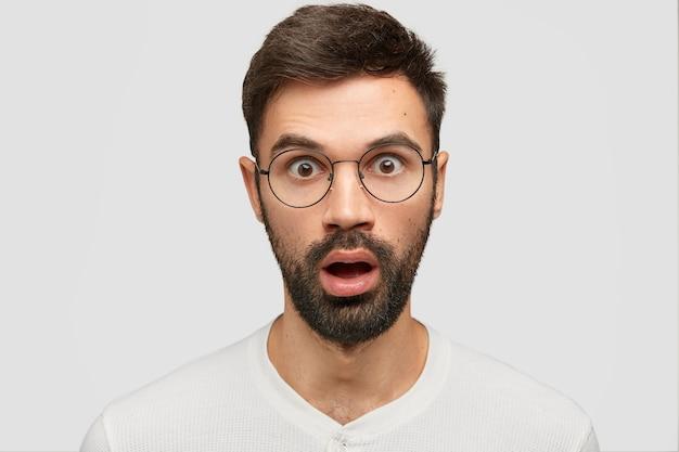 Tête d'un jeune homme européen stupéfait avec un chaume épais, regarde la caméra