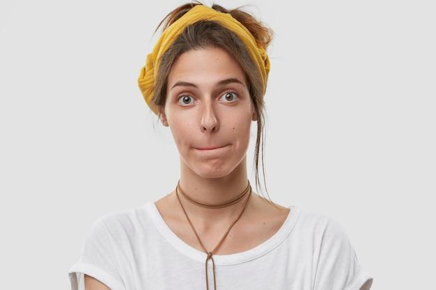 Tête de jolie femme presse les lèvres ensemble, a confondu l'expression du visage, regarde, porte un couvre-chef jaune sur la tête