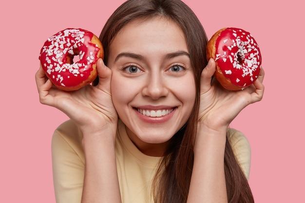 La tête de la jolie jeune femme européenne a une expression satisfaite, montre des dents blanches, tient de délicieux beignets