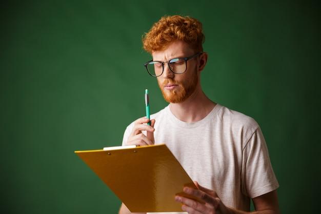 Tête de lecture sérieuse homme barbu en t-shirt blanc tenant un dossier et un stylo,