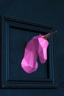Tête de licorne à la main origami violet dans un cadre bleu à partir d'une image d'un mur bleu