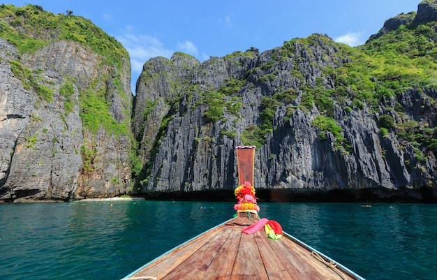 Tête longue queue de bateau sur la mer et la falaise rocheuse fond de montagne