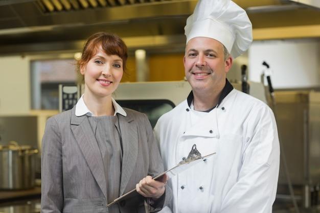 Tête mature cuisinier posant avec le directeur féminin