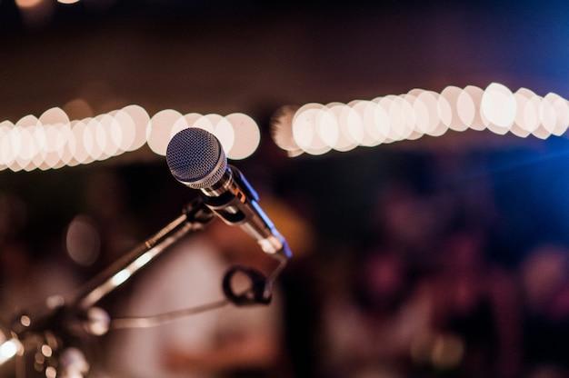 Tête de micro sur scène dans une pièce sombre. concerts, mini concerts et festivals de musique.