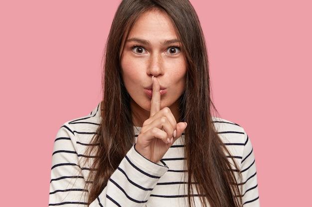 La tête d'une mystérieuse jeune femme choquée exige un silence complet et fait un geste de silence
