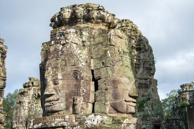 Tête de pierre sur les tours du temple bayon à angkor thom, cambodge