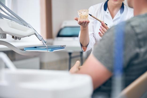 Tête recadrée de femme tenant un modèle de mâchoire tout en parlant avec un homme dans un fauteuil dentaire au bureau