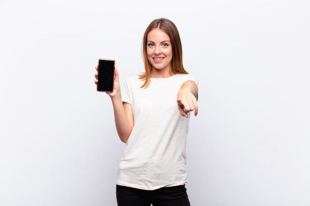 Tête rouge jolie femme pointant sur la caméra avec un sourire satisfait, confiant et amical, vous choisissant tenant un smartphone