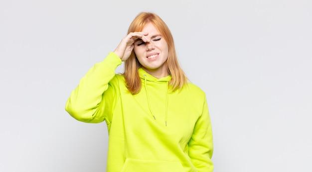 Tête rouge jolie femme à la recherche de stressé, fatigué et frustré, séchant la sueur du front, se sentant désespérée et épuisée