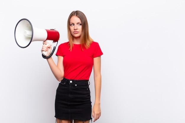 Tête rouge jolie femme se sentant triste, contrariée ou en colère et regardant de côté avec une attitude négative, fronçant les sourcils en désaccord avec un mégaphone