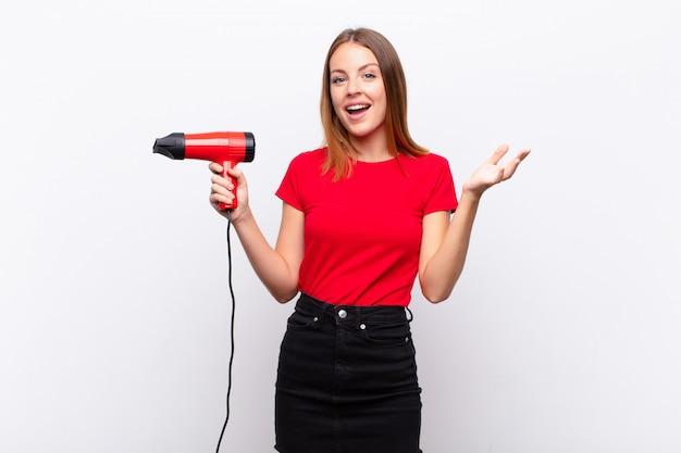 Tête rouge jolie femme se sentir heureuse, surprise et joyeuse, souriant avec une attitude positive, réalisant une solution ou une idée tenant un coiffeur