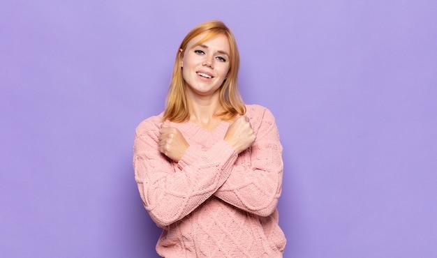 Tête rouge jolie femme souriant joyeusement et célébrant, les poings serrés et les bras croisés, se sentant heureux et positif