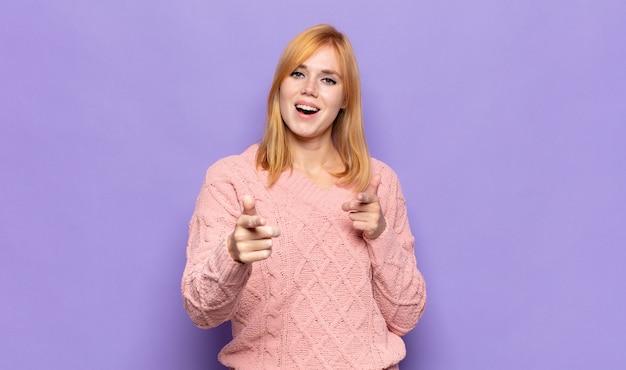 Tête rouge jolie femme souriante avec une attitude positive, réussie et heureuse pointant vers la caméra, faisant signe des armes à feu avec les mains