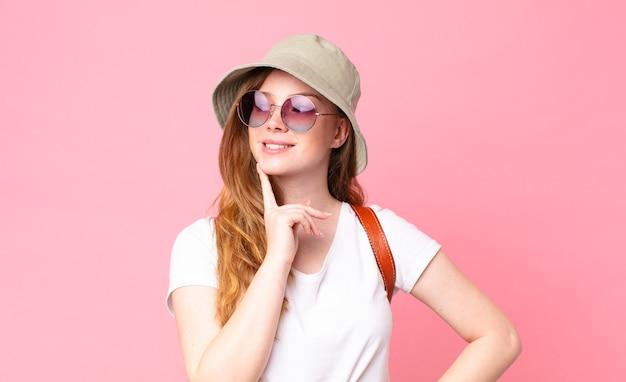 Tête rouge jolie femme touriste souriant joyeusement et rêvant ou doutant