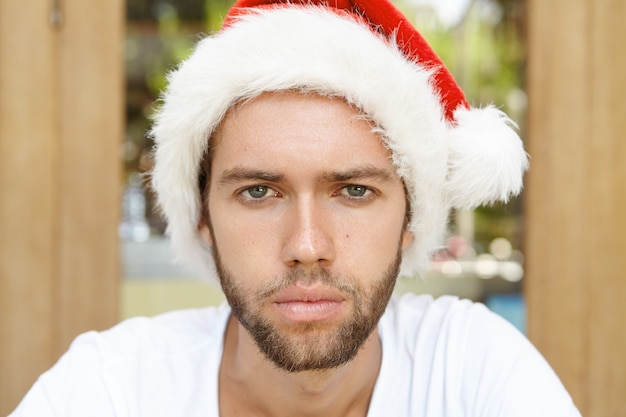 Tête de séduisant jeune homme mal rasé portant un chapeau de père noël à la malheureuse