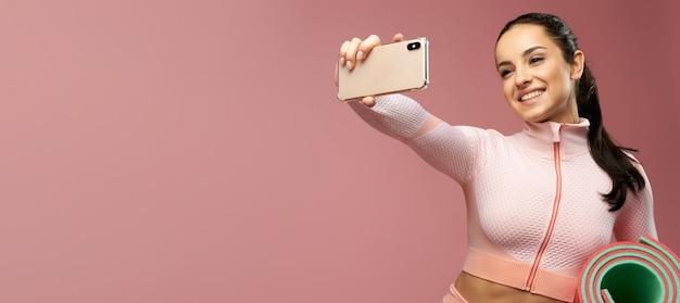 En-tête de site web de jeune femme gaie avec le tapis de yoga faisant le selfie