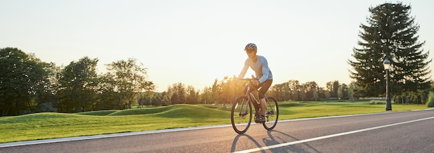 En-tête de site web de vue arrière d'un homme athlétique en tenue de sport debout avec un vélo sur le