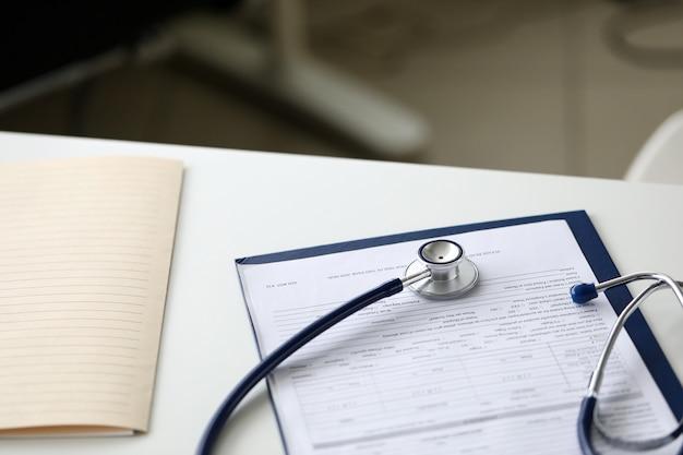 Tête de stéthoscope couché sur un document papier médical