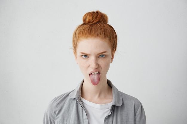 Tête de vilaine fille d'apparence européenne qui sort la langue, essayant de taquiner quelqu'un, l'air immature et offensant, toute son apparence exprimant la grossièreté et le dégoût. signes, symboles