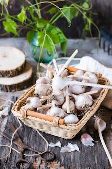 Têtes d'ail dans un panier en osier sur une table en bois