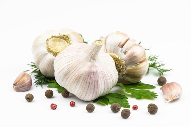 Têtes d'ail, feuilles vertes de persil et d'aneth, piment fort et parfumé isolé sur fond blanc.