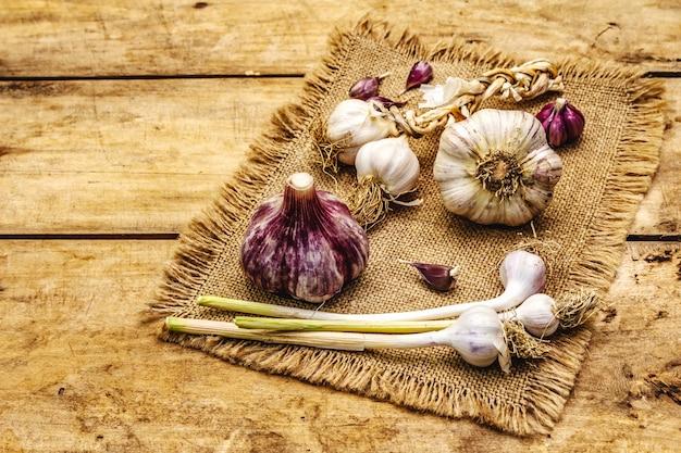 Têtes d'ail et gousses d'ail entières non pelées. nouvelle récolte, sur un sac, fond de planches de bois, espace copie