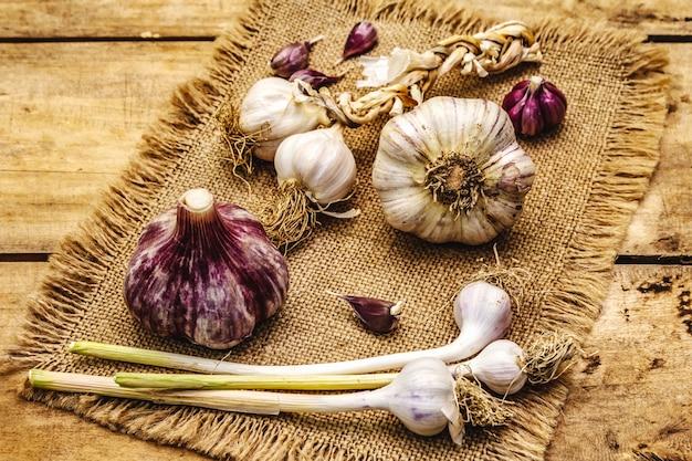 Têtes d'ail et gousses d'ail entières non pelées. nouvelle récolte, sur un sac, fond de planches de bois, gros plan