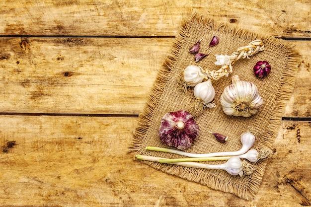 Têtes d'ail et gousses d'ail entières non pelées. nouvelle récolte, sur un sac, fond de planches de bois, vue du dessus
