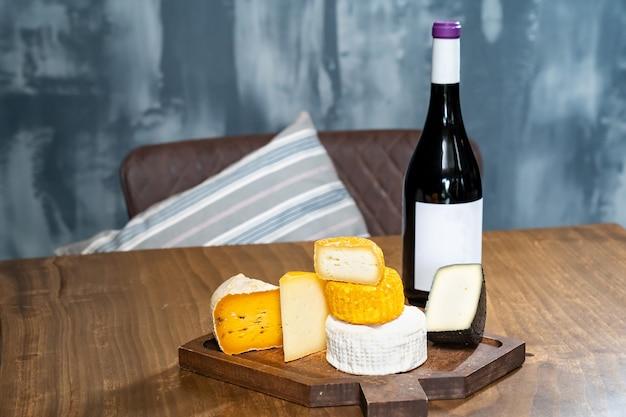 Têtes de fromages assorties sur une planche à découper et une bouteille de vin sur une table en bois. une fromagerie avec un café.