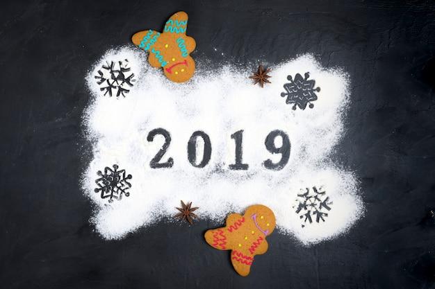 Texte de 2019 fait avec de la farine avec des décorations sur fond noir au pain d'épice noël