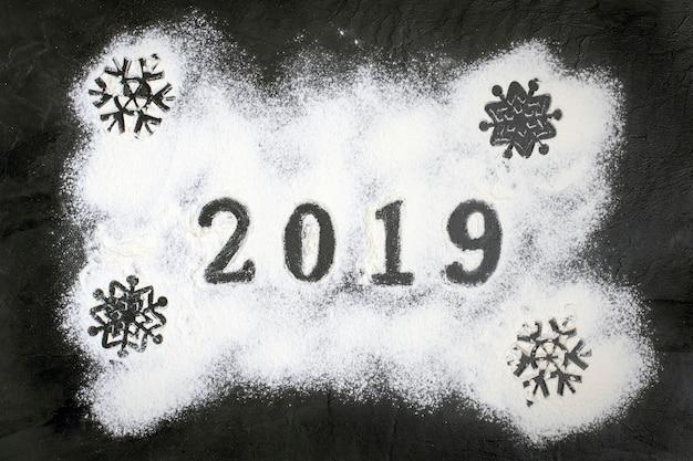 Texte de 2019 fait avec de la farine avec des décorations sur fond noir. joyeux noël, h