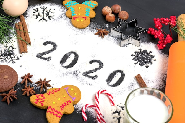 Texte 2020 fait avec de la farine avec des décorations sur fond noir. lay plat.