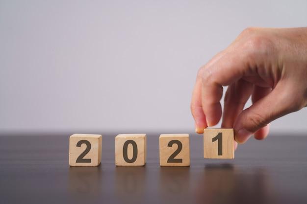 Texte 2021 sur cube en bois isolé sur gris. concept de compte à rebours du nouvel an.