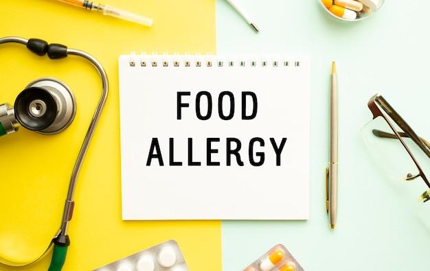 Texte allergie alimentaire sur ordinateur portable avec stéthoscope et stylo sur jaune