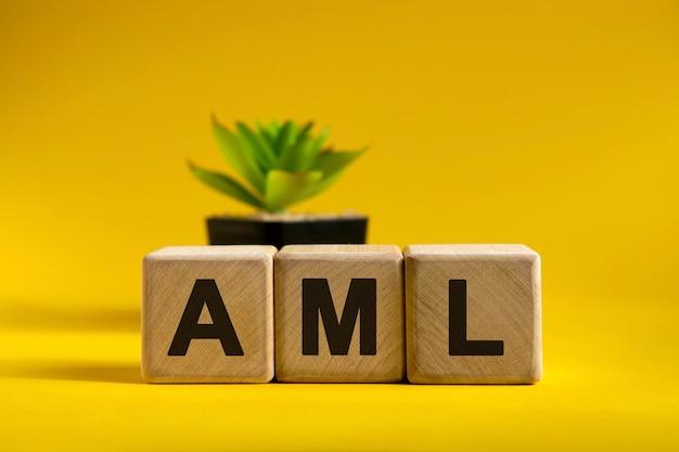 Texte aml sur des cubes en bois sur une surface et un pot noir avec une fleur