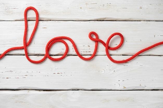 Texte d'amour de corde rouge sur fond en bois blanc