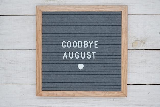 Texte en anglais au revoir août et un signe de coeur sur une planche de feutre gris dans un cadre en bois.