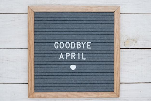 Texte en anglais au revoir avril et un signe de coeur sur une planche de feutre gris dans un cadre en bois.