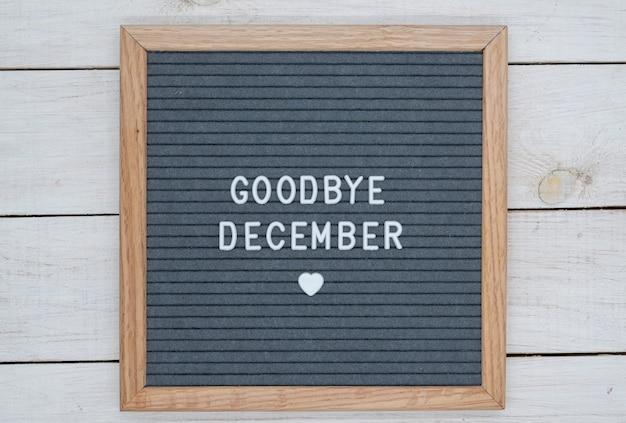 Texte en anglais au revoir décembre et un signe de coeur sur une planche de feutre gris dans un cadre en bois.
