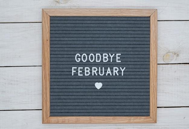 Texte en anglais au revoir février et un signe de coeur sur une planche de feutre gris dans un cadre en bois.