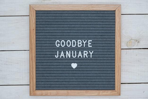 Texte en anglais au revoir janvier et un signe de coeur sur une planche de feutre gris dans un cadre en bois.