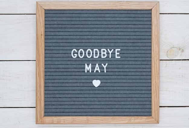 Texte en anglais au revoir mai et un signe de coeur sur une planche de feutre gris dans un cadre en bois.