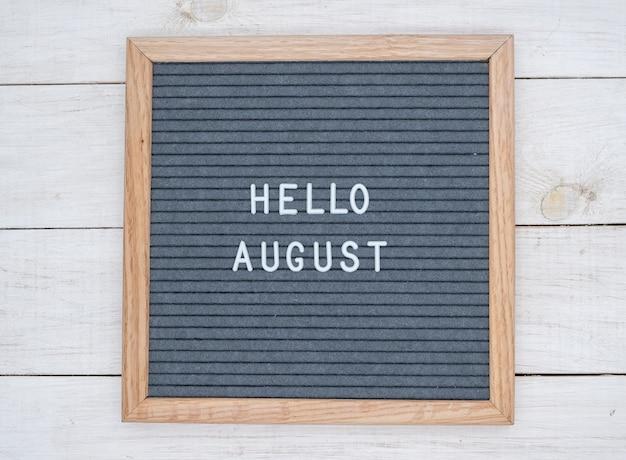 Texte anglais bonjour août sur un tableau de lettres en lettres blanches