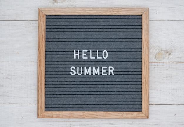 Texte anglais bonjour l'été sur un tableau de lettres en lettres blanches
