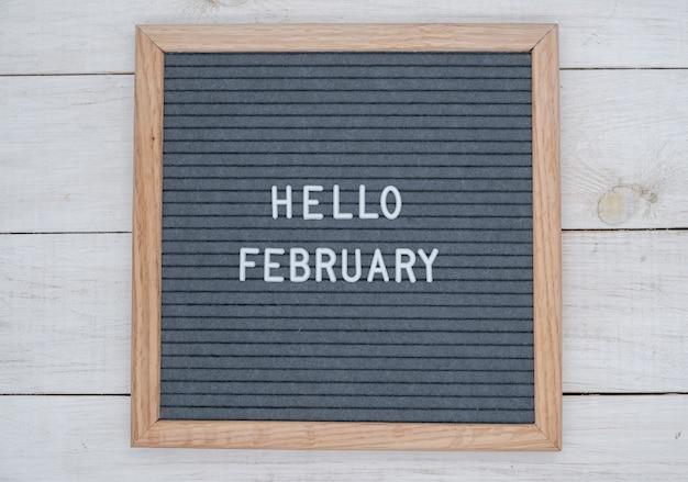 Texte anglais bonjour février sur un tableau de lettres en lettres blanches